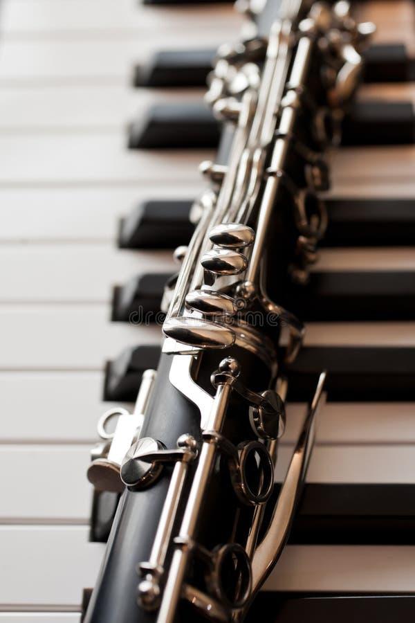 Klarinett som ligger på pianotangenter royaltyfria foton