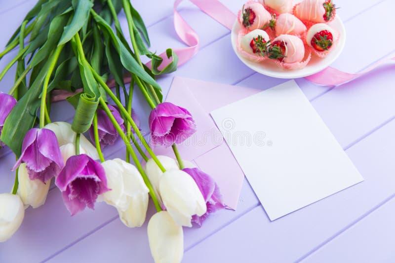 Klart ark av papper med kuvertet, jordgubbe i choklad, bukett av vita och purpurfärgade tulpan och det rosa bandet på den lila ta royaltyfri bild