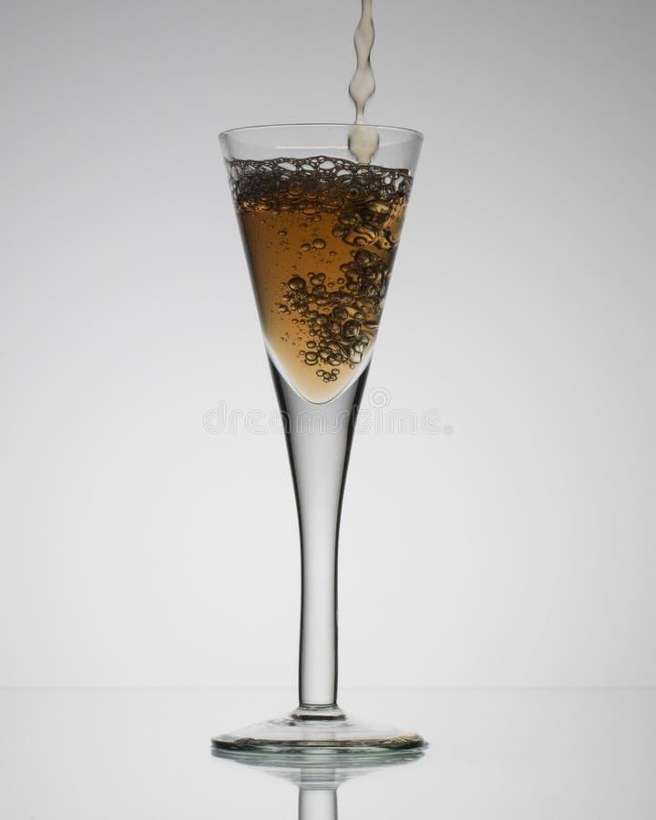 Klart exponeringsglas med en drink som in häller royaltyfri bild