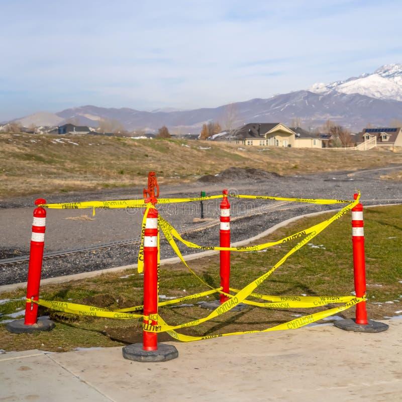 Klart fyrkantigt band för trafikpoler som med försiktighet omger ett hål i jordningen nära en järnväg royaltyfri foto