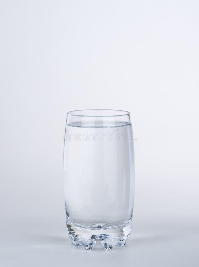 Klart glass mycket av vatten på vit bakgrund arkivfoton