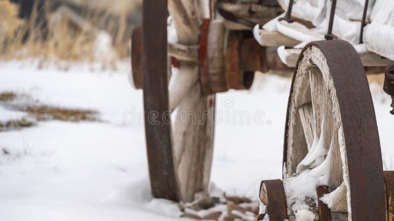 Klart panoramaslut upp av de rostiga hjulen av en gammal trävagn som beskådas i vinter royaltyfri bild