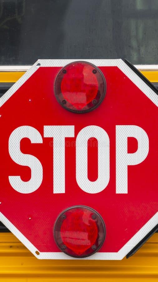 Klart vertikalt slut upp av ett oktogon format rött stopptecken med signalljus på en skolbuss royaltyfri foto