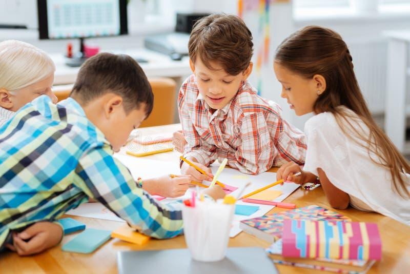 Klasgenoten die beelden zich in een klaslokaal samentrekken stock foto