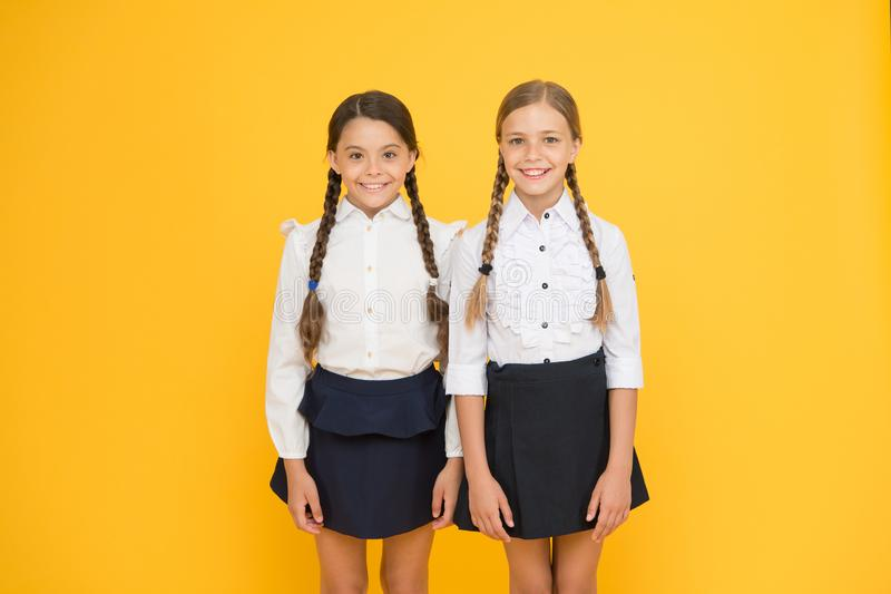 Klasgenoten die pret hebben bij de aanbiddelijke leerlingen van schoolvrienden Perfecte eenvormige school van de schoolmeisjes de royalty-vrije stock fotografie