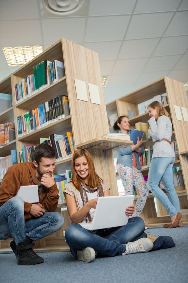 Klasgenoten die samen op laptop in bibliotheek bestuderen royalty-vrije stock foto