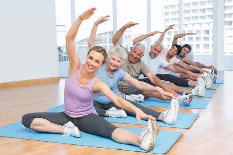 Klasse, die Hände an der Yogaklasse ausdehnt stockbild