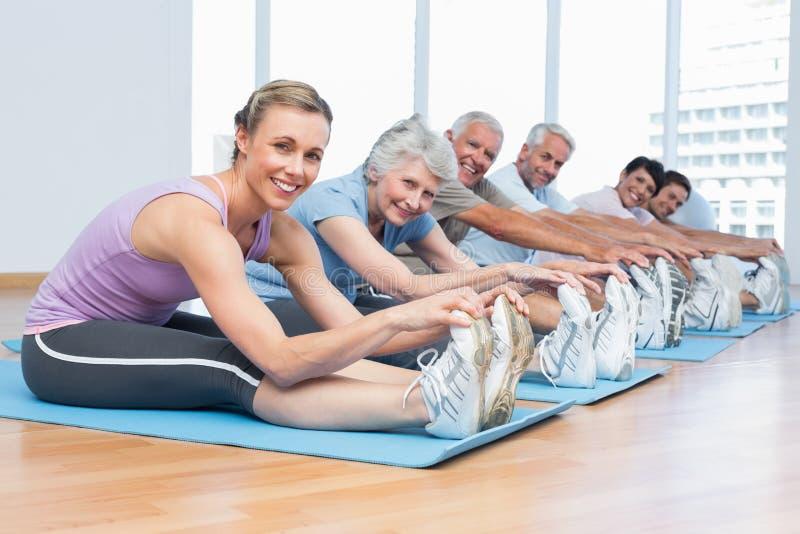 Klasse het uitrekken zich handen aan benen bij yogaklasse royalty-vrije stock foto's