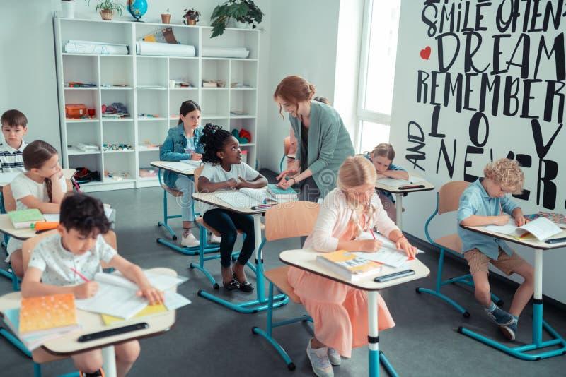 Klasse van kinderen die aan hun taak tijdens de les werken stock foto's