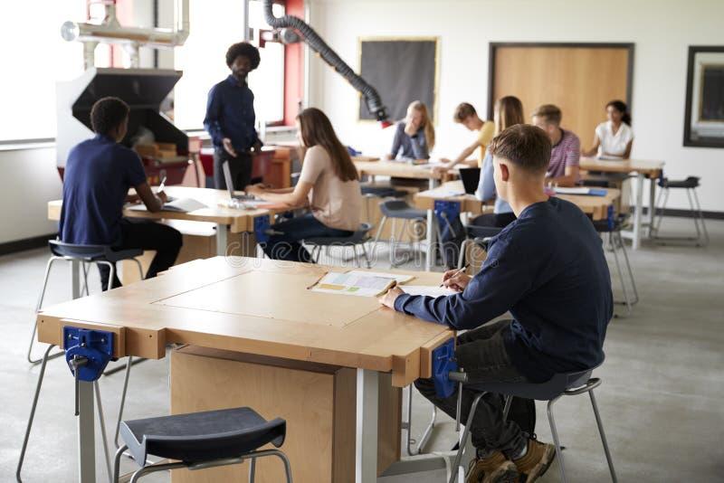 Klasse van Middelbare schoolstudenten die bij het Werkbanken zitten die aan de Technologieles van Leraarsin design and luisteren royalty-vrije stock fotografie