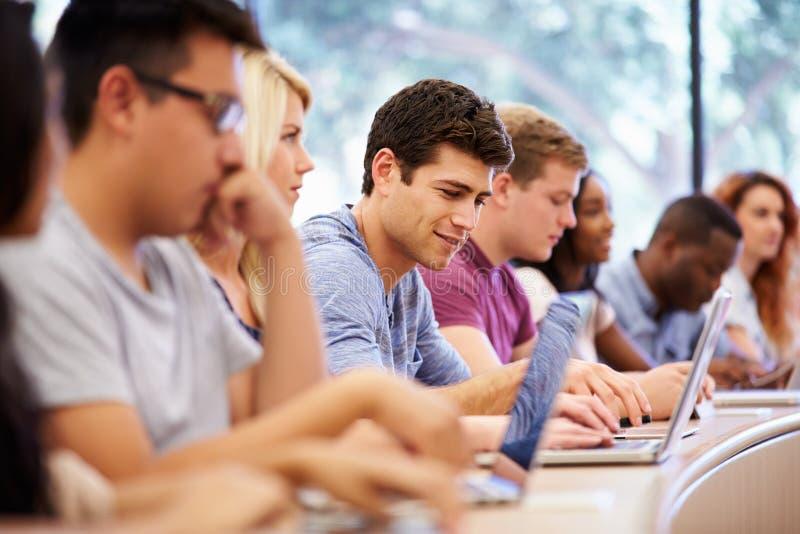 Klasse von den Hochschulstudenten, die Laptops im Vortrag verwenden lizenzfreie stockfotos