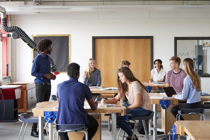 Klasse von den hohen Schülern, die an den Werkbänken hörend auf Lehrer-In Design And-Technologie-Lektion sitzen lizenzfreie stockfotografie