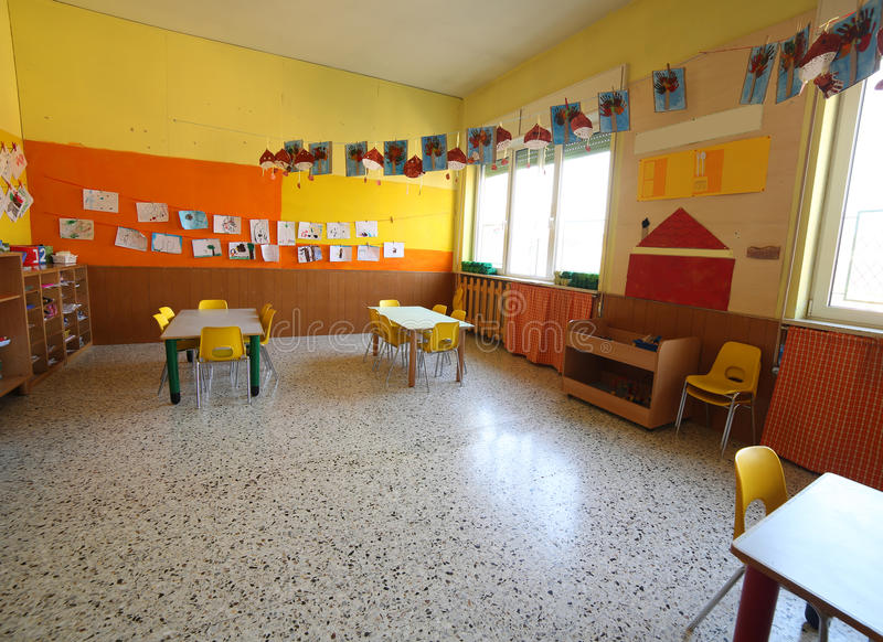 Klassenzimmer einer Kindheitskindertagesstätte mit Zeichnungen und den Tabellen stockfoto