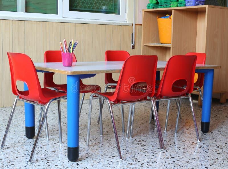 Klassenzimmer eines Kindergartens mit roten Stühlen und kleinem Schulvorsprung stockbilder