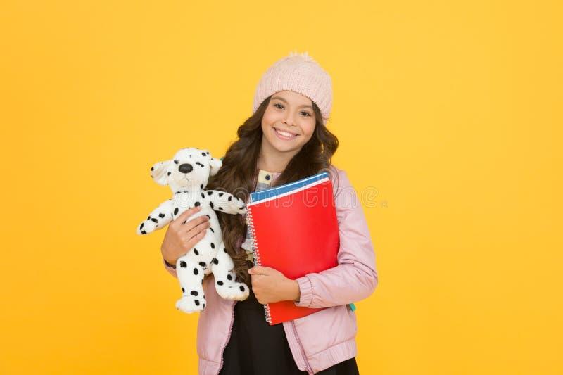 Klasserna börjar glad liten flicka som håller i leksakshund vintersemester och semester barnlycka utveckling av barnomsorg royaltyfria foton