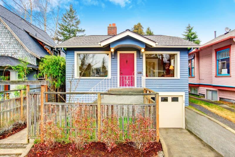 Klassiek Amerikaans huis buiten met blauwe versiering en rode voordeur stock foto