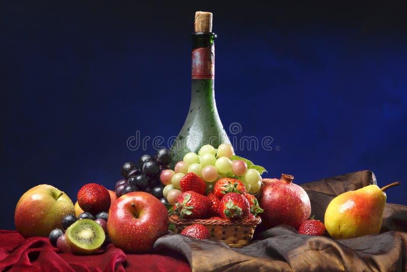 Klassiek Nederlands stilleven met stoffige horizontale fles wijn en vruchten op een donkerblauwe achtergrond, royalty-vrije stock fotografie