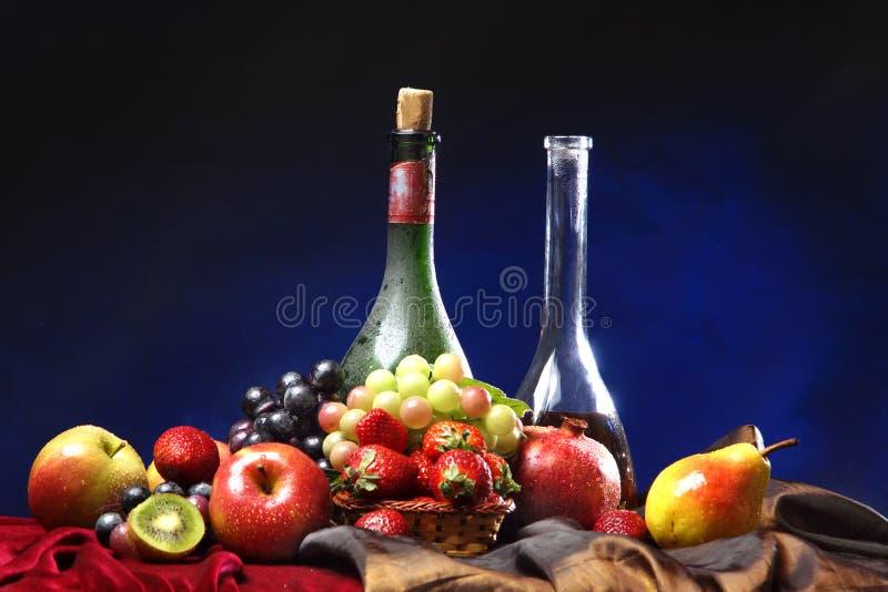 Klassiek Nederlands stilleven met twee horizontale flessen wijn en natte vruchten op een donkerblauwe achtergrond, royalty-vrije stock fotografie