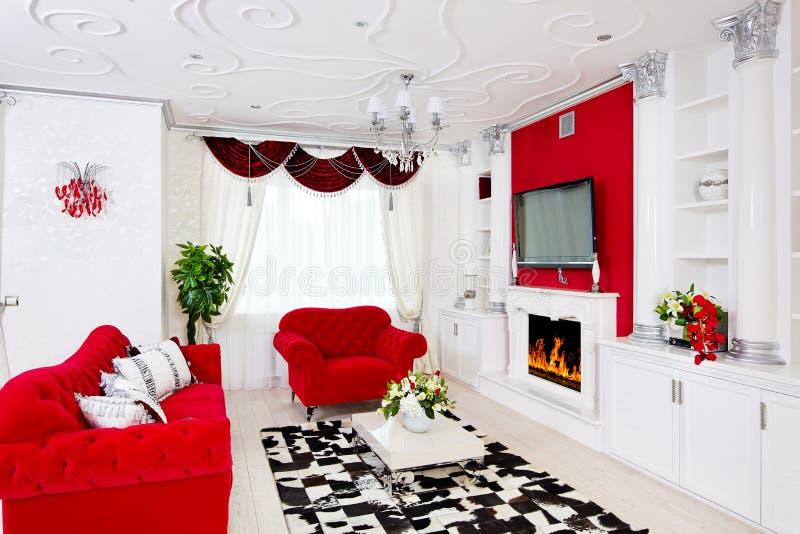 Klassiek rood woonkamerbinnenland met brandplaats, rode furnitur royalty-vrije stock foto's
