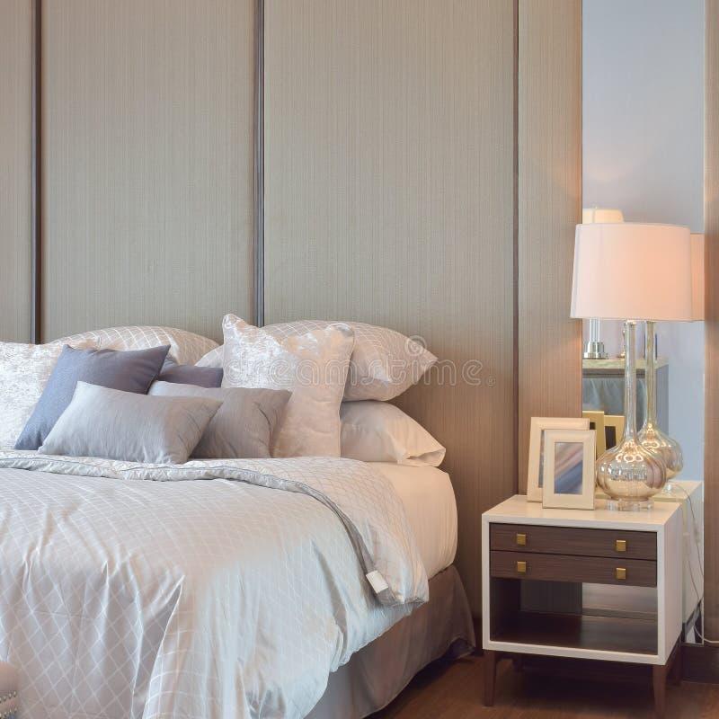 Klassiek slaapkamerbinnenland met hoofdkussens en lezingslamp op bedlijst stock foto