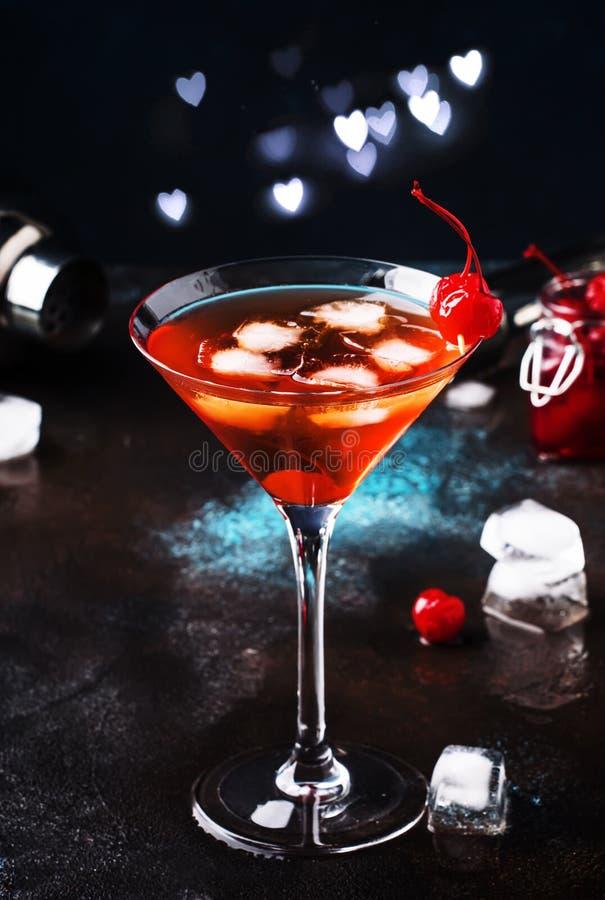 Klassieke alcoholische cocktail Manhattan met bourbon, rode vemuth, bittere, ijs en cocktailkers in glas, grijze barteller royalty-vrije stock fotografie
