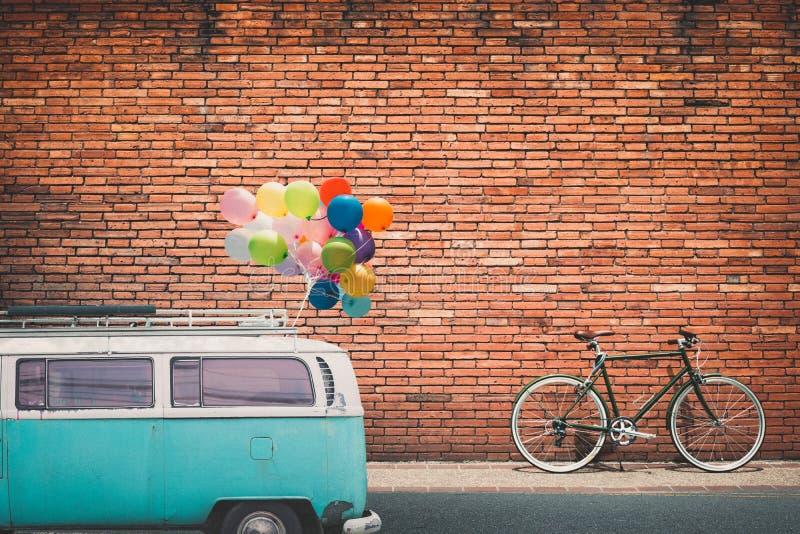 Klassieke auto uitstekende bestelwagen in stad met kleurrijke die ballon op dak op weg in stedelijk wordt geparkeerd royalty-vrije stock foto's
