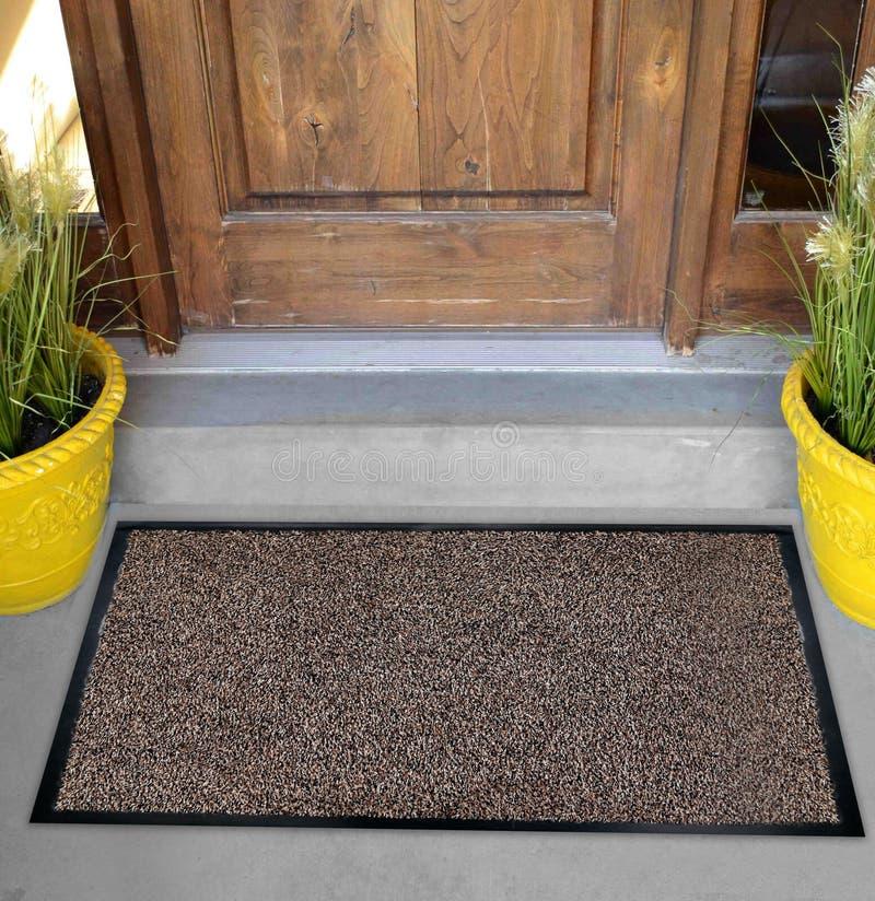 Klassieke Beige zwarte grijze welkome deurmat met zwarte grens buiten huis met gele bloemen en bladeren stock afbeeldingen