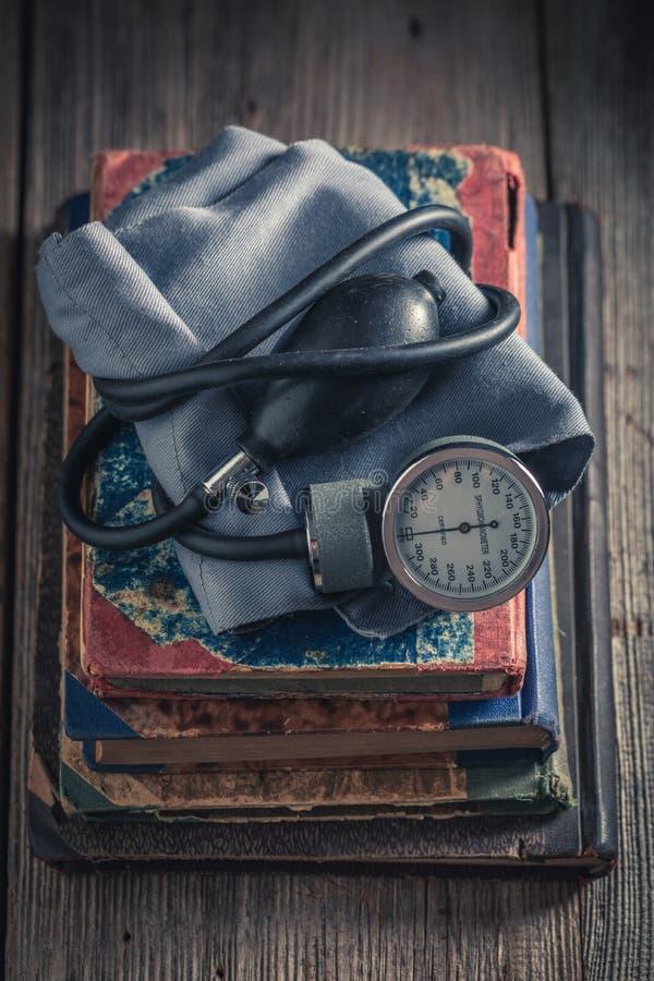Klassieke bloeddrukmeter op de stapel van oude boeken stock fotografie