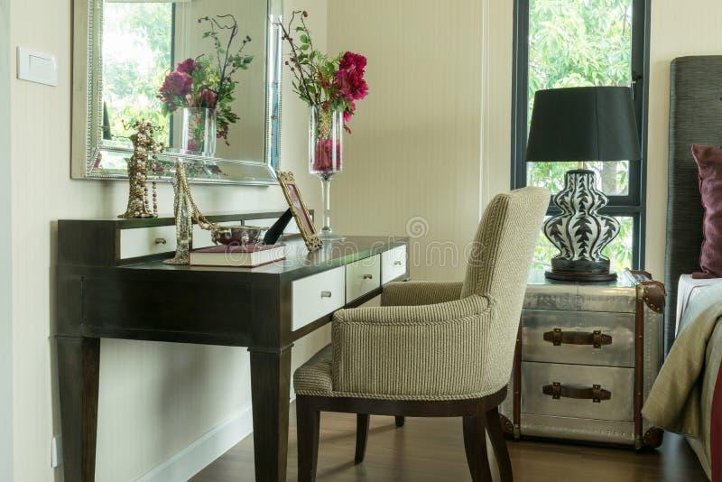 Klassieke bruine die stoel met juwelen op toilettafel worden geplaatst stock foto