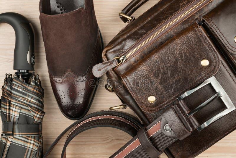Klassieke bruine schoenen, aktentas, riem en paraplu op bureau Mening van hierboven stock fotografie