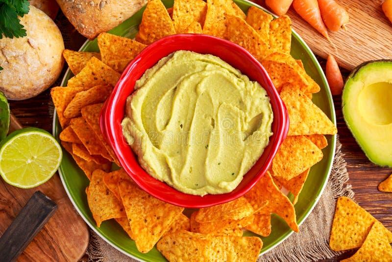 Klassieke Eigengemaakte avocadohummus met olijfolie, wortelen, pitabroodjespaanders, kalk, Spaanse pepers, peterselie stock fotografie