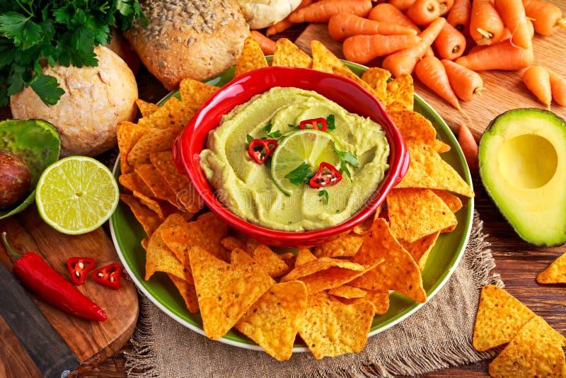 Klassieke Eigengemaakte avocadohummus met olijfolie, wortelen, pitabroodjespaanders, kalk, Spaanse pepers, peterselie stock foto's