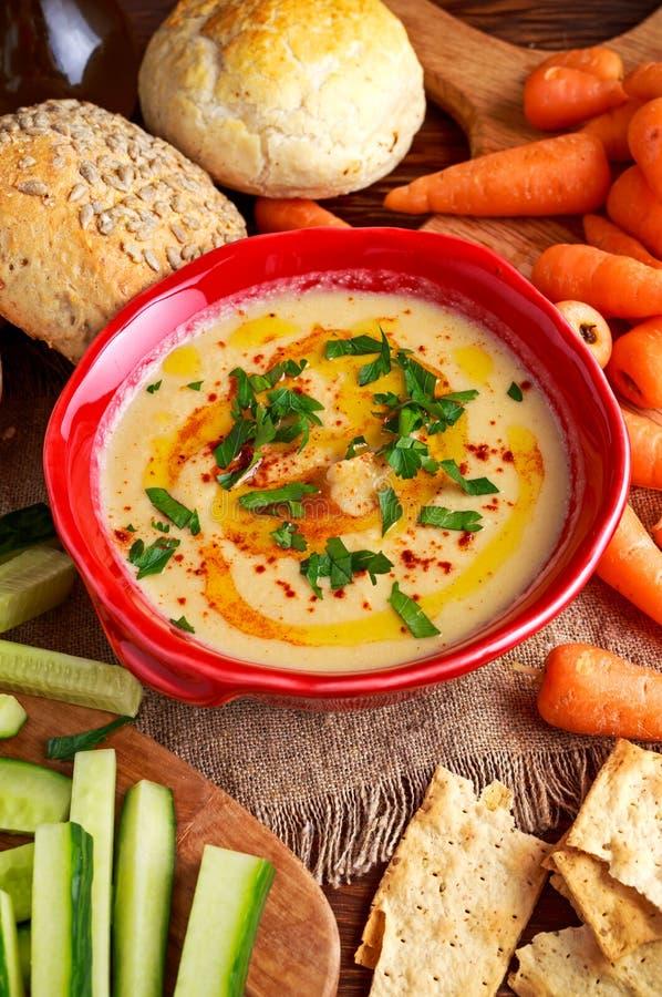 Klassieke Eigengemaakte hummus met olijfolie, wortelen, komkommer, flatbread, peterselie stock fotografie
