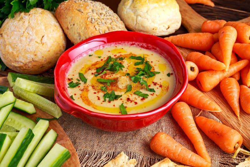 Klassieke Eigengemaakte hummus met olijfolie, wortelen, komkommer, flatbread, peterselie royalty-vrije stock foto's