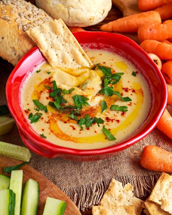 Klassieke Eigengemaakte hummus met olijfolie, wortelen, komkommer, flatbread, peterselie royalty-vrije stock fotografie