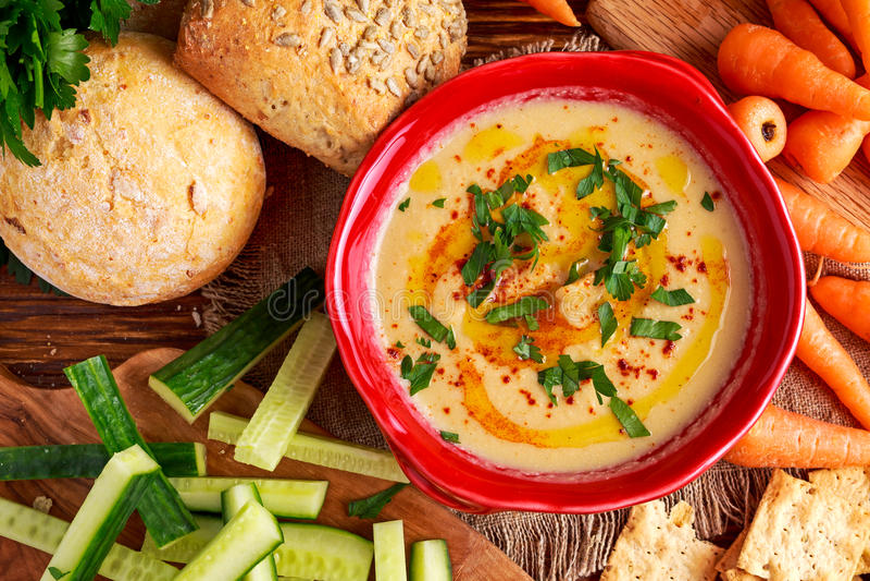 Klassieke Eigengemaakte hummus met olijfolie, wortelen, komkommer, flatbread, peterselie royalty-vrije stock foto