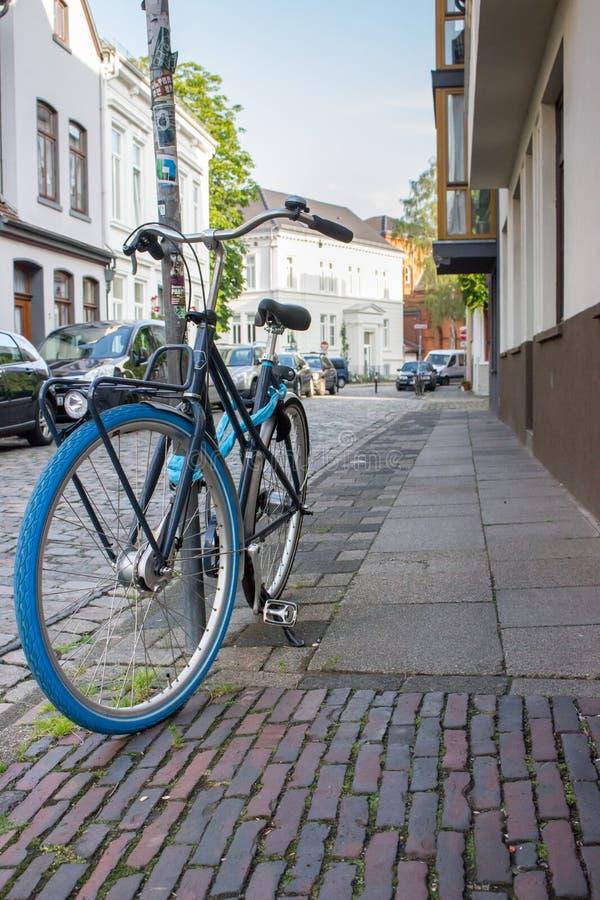 Klassieke fiets met blauwe wielen op stadsstraat Stadsvervoerconcept Parkerenfiets in stad Antieke fiets op straat royalty-vrije stock foto's