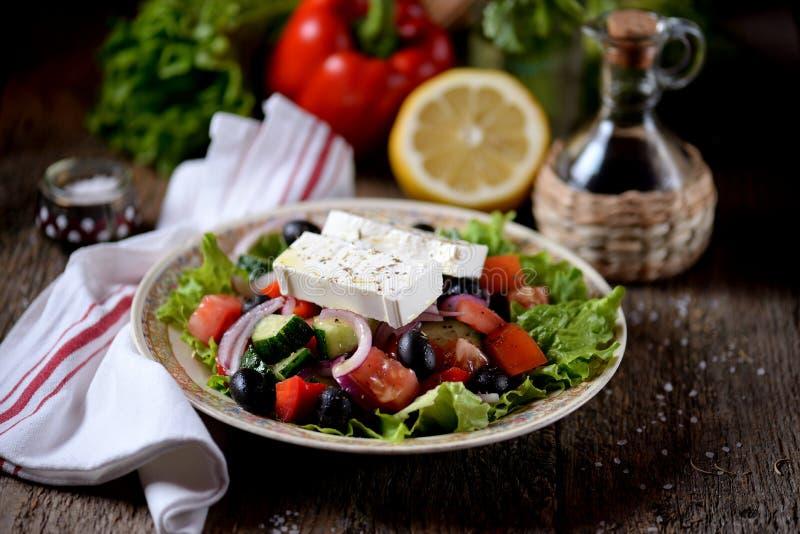 Klassieke Griekse salade van tomaten, komkommers, Spaanse peper, ui met olijven, orego en feta-kaas stock foto's