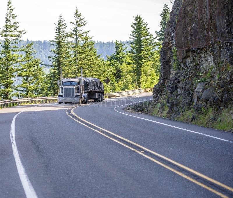 Klassieke grote installatie semi vrachtwagen die behandelde lading op vlakke bed semi aanhangwagen vervoeren die op de berg winde stock fotografie