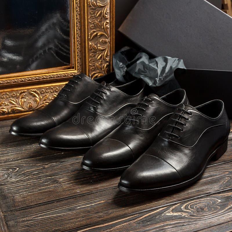 Klassieke mannelijke zwarte leerschoenen met gouden kleurenomlijsting stock fotografie