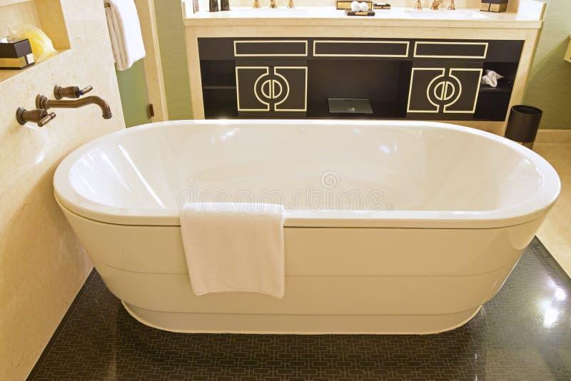 Klassieke ontwerpbadkamers met geïsoleerde badkuip, marmeren muur en versace geïnspireerde kabinetsdeur royalty-vrije stock afbeelding