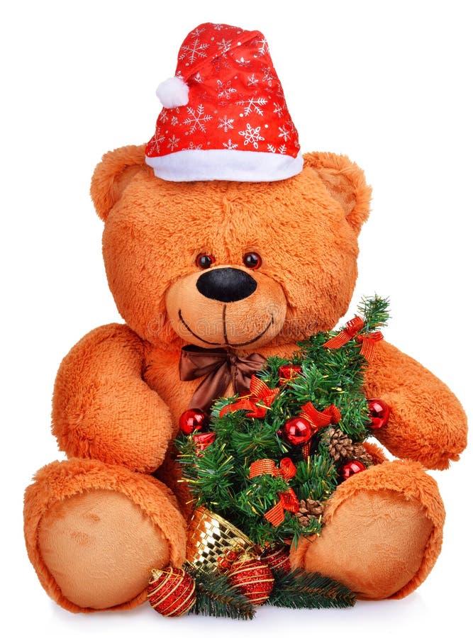 Klassieke teddybeer in rode hoed met Kerstmisboom royalty-vrije stock fotografie