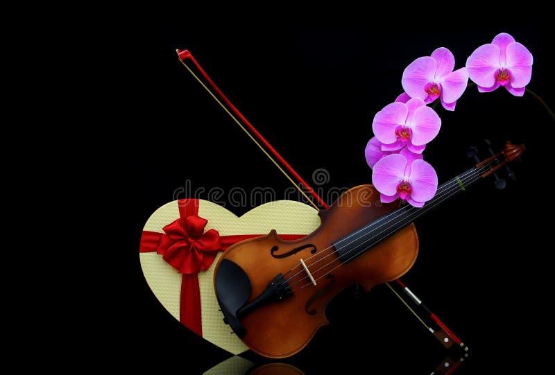 Klassieke viool met boeg, hartvormig cadeaudoosje en roze orchideeën op donkere achtergrond stock afbeeldingen