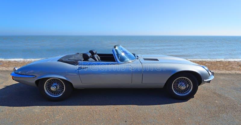 Klassieke Zilveren het Type van Jaguar E convertibele die Auto op Strandboulevardpromenade wordt geparkeerd stock foto