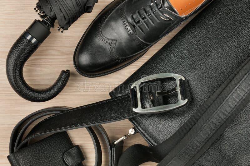 Klassieke zwarte schoenen, aktentas, riem en paraplu op bureau Mening van hierboven royalty-vrije stock fotografie