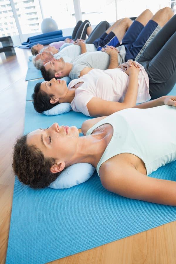 Klassificera att vila på mats i rad på yogagrupp royaltyfri foto