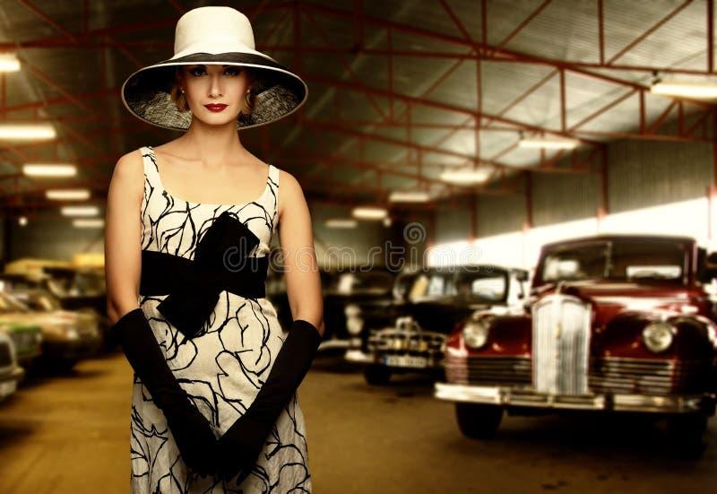 Klassikerkvinna mot retro bilar arkivbild