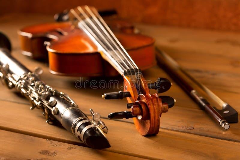 Klassikermusikfiol och klarinett i tappningträ arkivbild