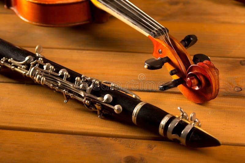 Klassikermusikfiol och klarinett i tappningträ fotografering för bildbyråer