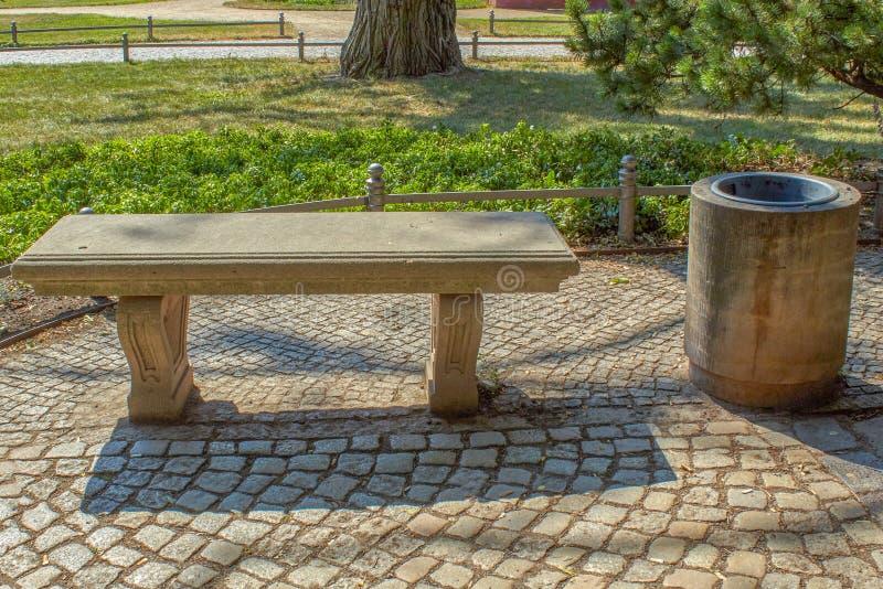 Klassikern parkerar bänken gjorde av stenen med avfall royaltyfria bilder